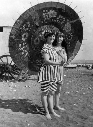 Models in bathing costumes posing for the camera at the beach, c 1910
