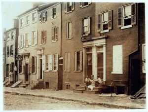 PLAY: Group of children playing on the stoop of a house next to 229 Tatnall St., a reputed house of prostitution. Investigator, Edward F. Brown. Location: Wilmington, Delaware 1910